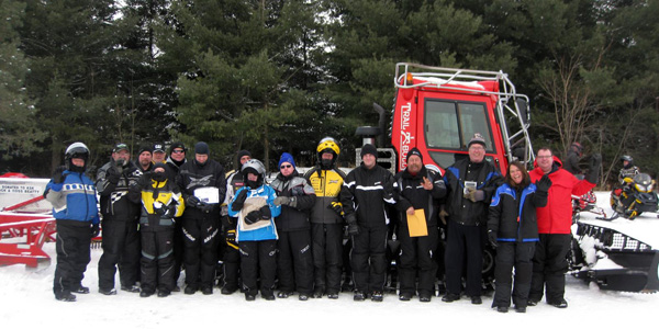 All the kemptville snowarama riders pose in front of a plow