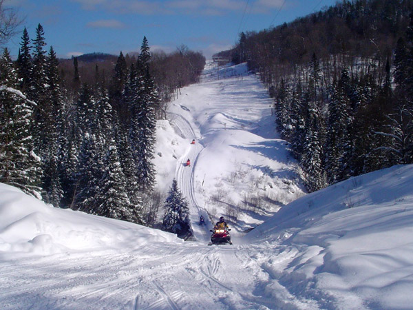 A snowmobile comes up the hills of the long scenic trail