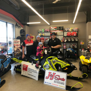 A family poses on a snowmobile inside J&J sports