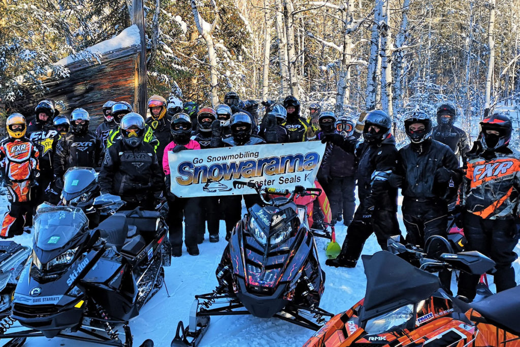 All the rider pose outside in their gear holding up a Snowarama banner