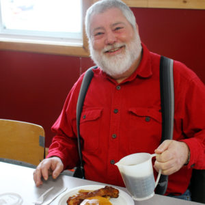 A man enjoys a pancake breakfast at last years event
