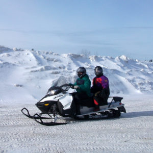 Two riders on a white snowmobile