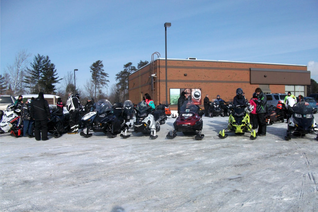 A line of snowmobiles waits outside