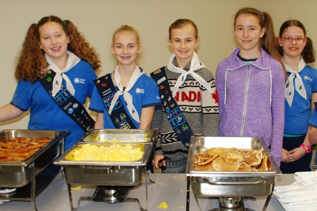 A girls group serves up breakfast