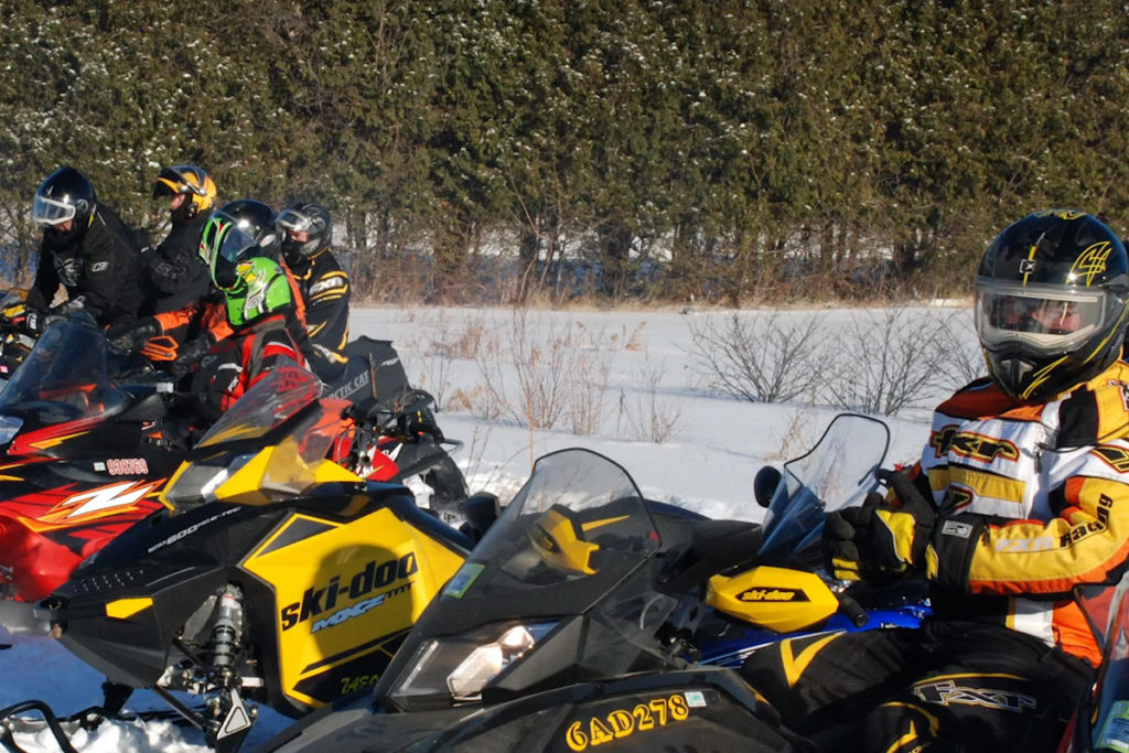 A line of snowmobiles waiting to go