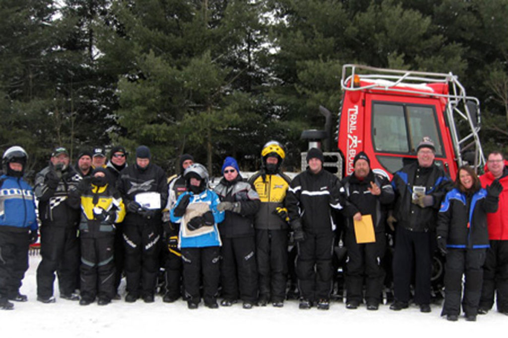 The riders pose in front of the big red trail grooming machine
