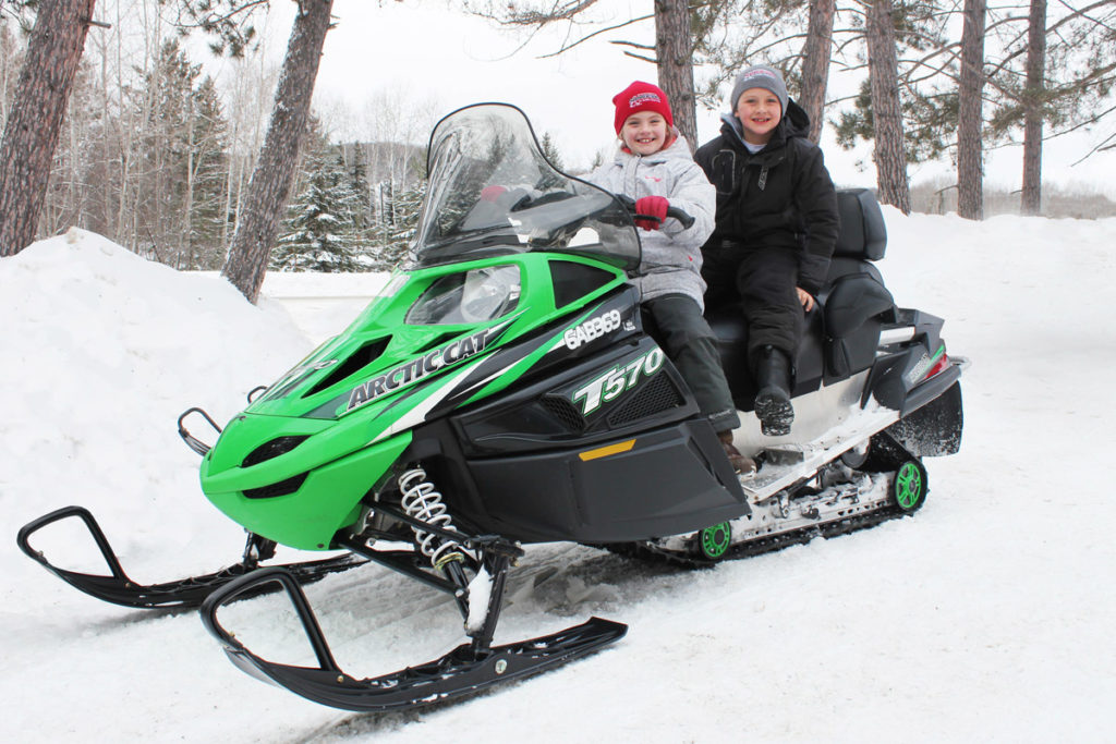 Two children on a green snowmobile