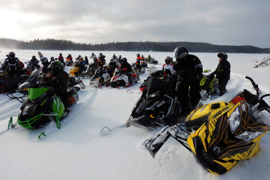 A snowmobile tipped in deep snow