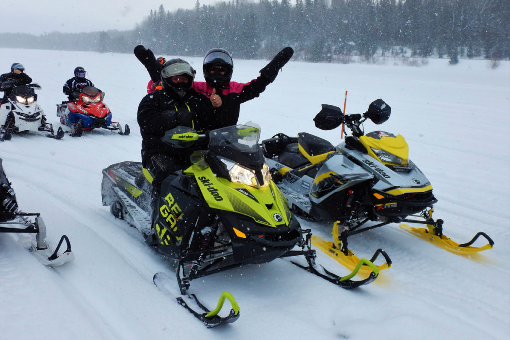 A rider gives a thumbs up while the passanger behind holds their arms wide