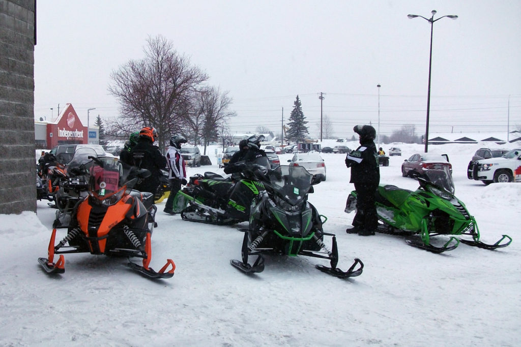 Snowmobiles gather outside a store