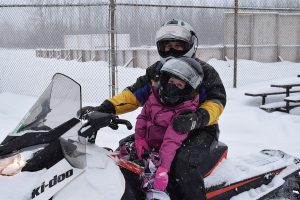 A rider and a little girl on a snowmobile