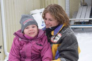 A rider and a little girl on a snowmobile with helmets off smiling